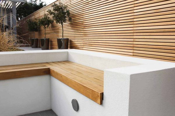 a white rendered wall with built in cedar seating and slatted fencing.