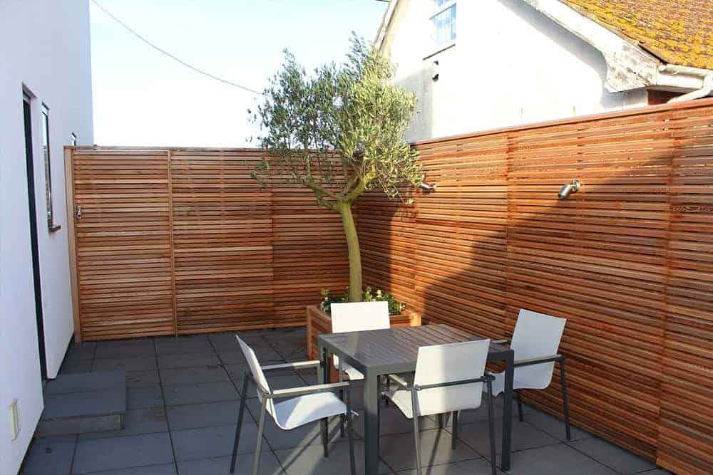 A view of a small garden area surrounded by cedar slatted fencing