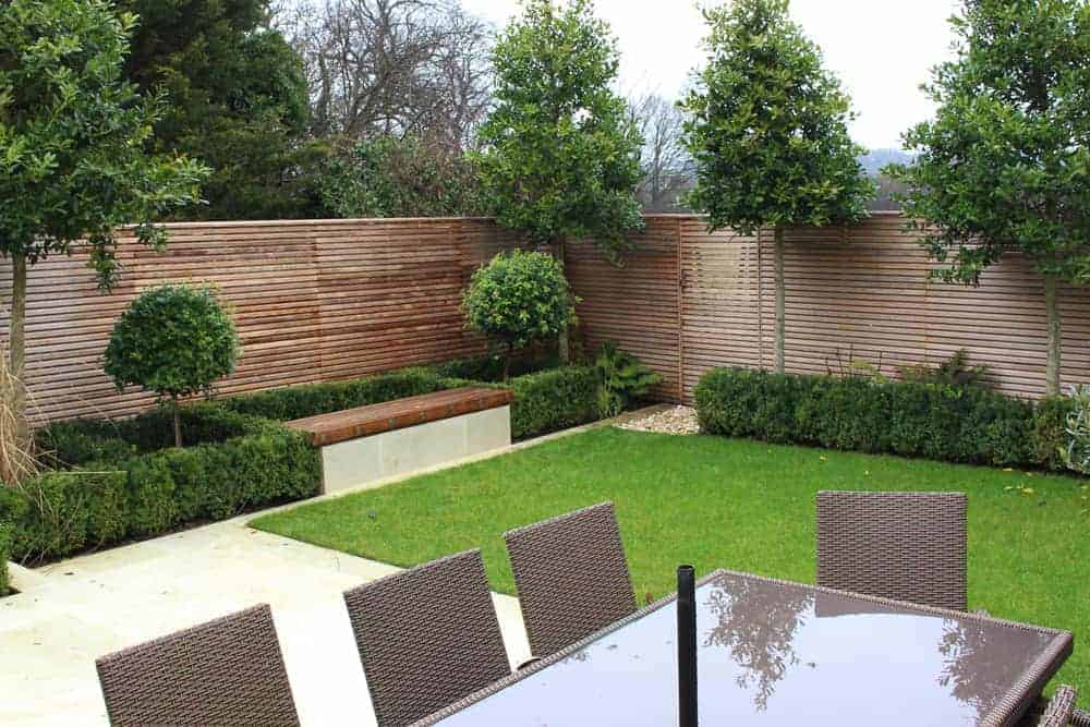 A view of a modern garden with cedar slatted fencing and gates.